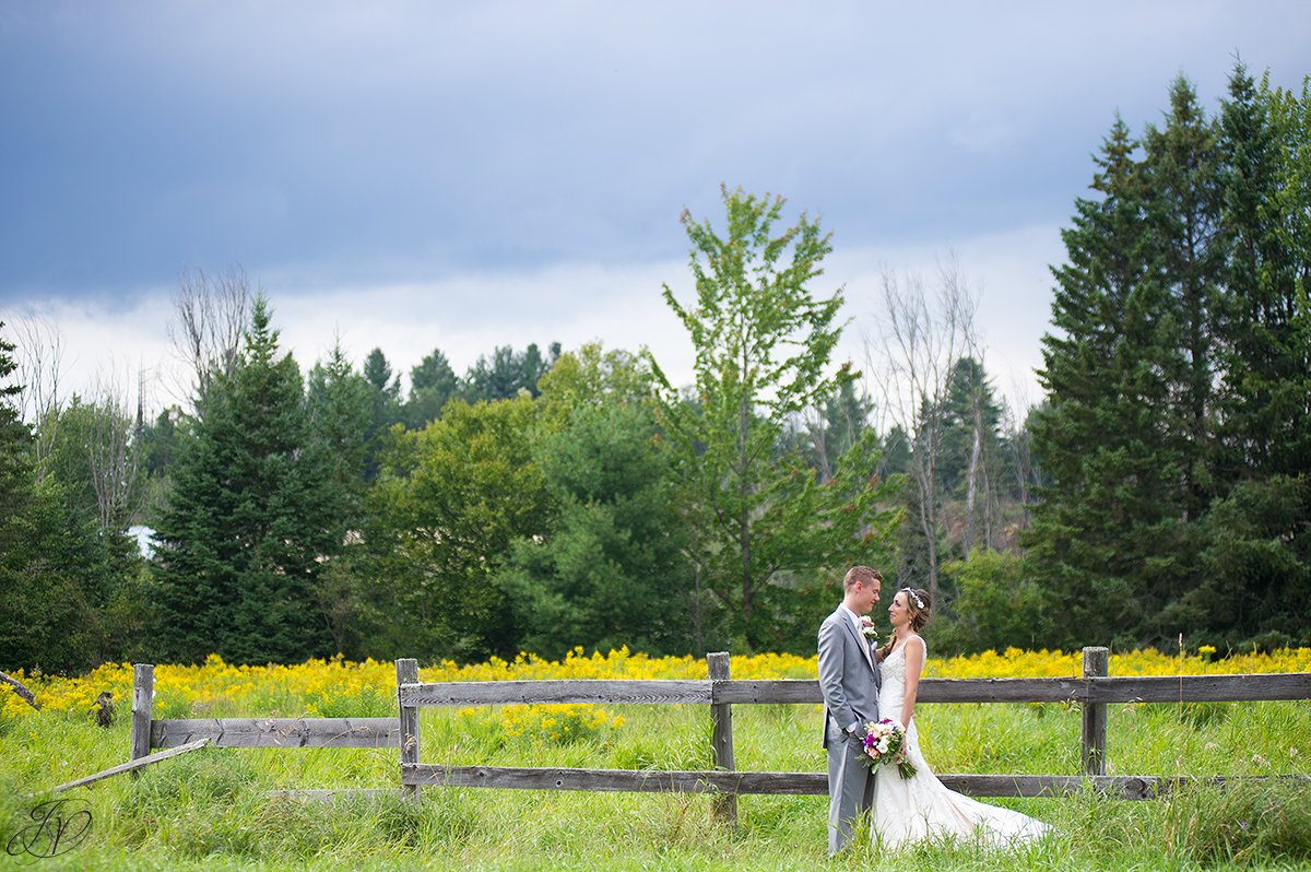 bride and groom near fence lake placid yellow flowers
