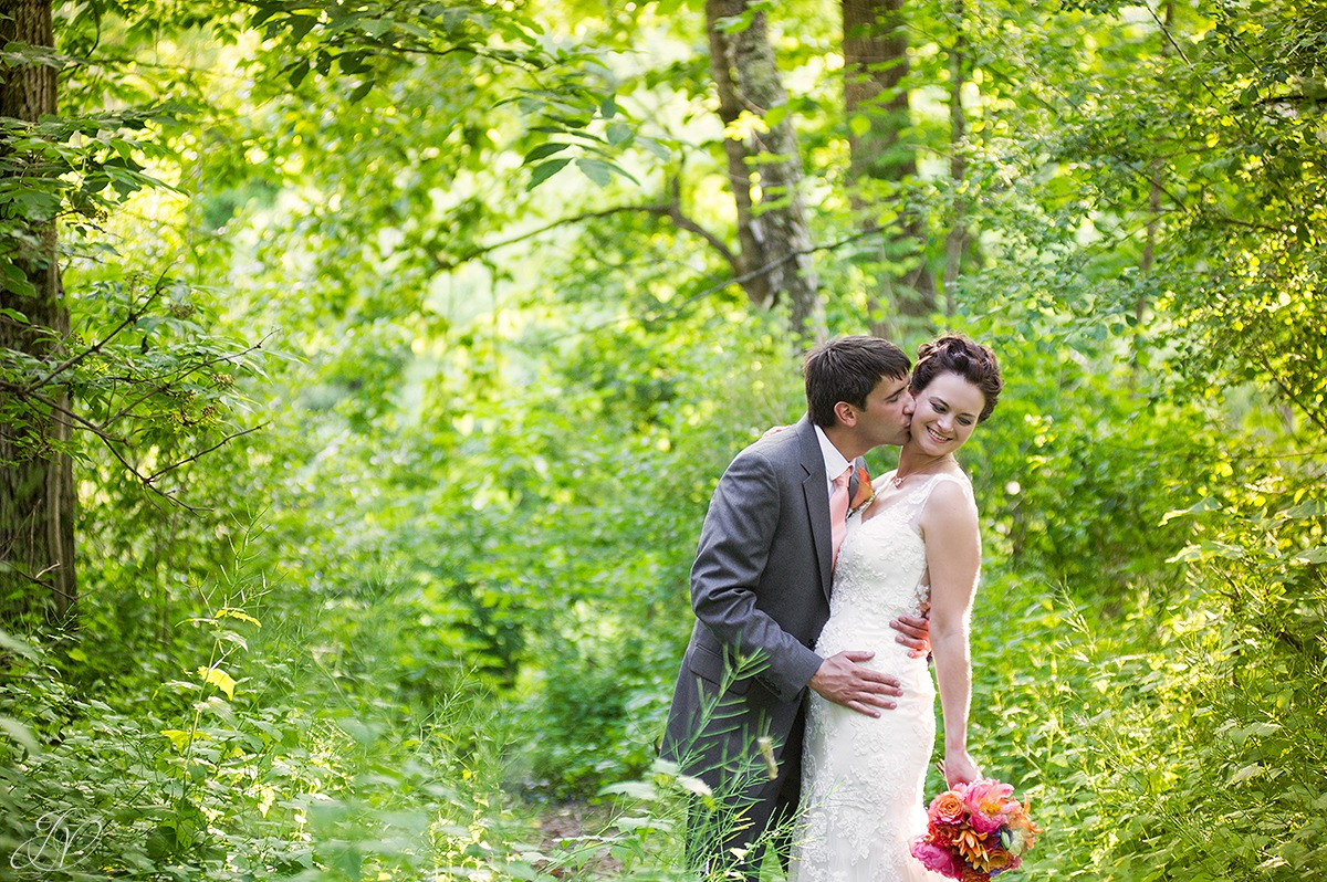 romantic shot of groom kissing bride in woods