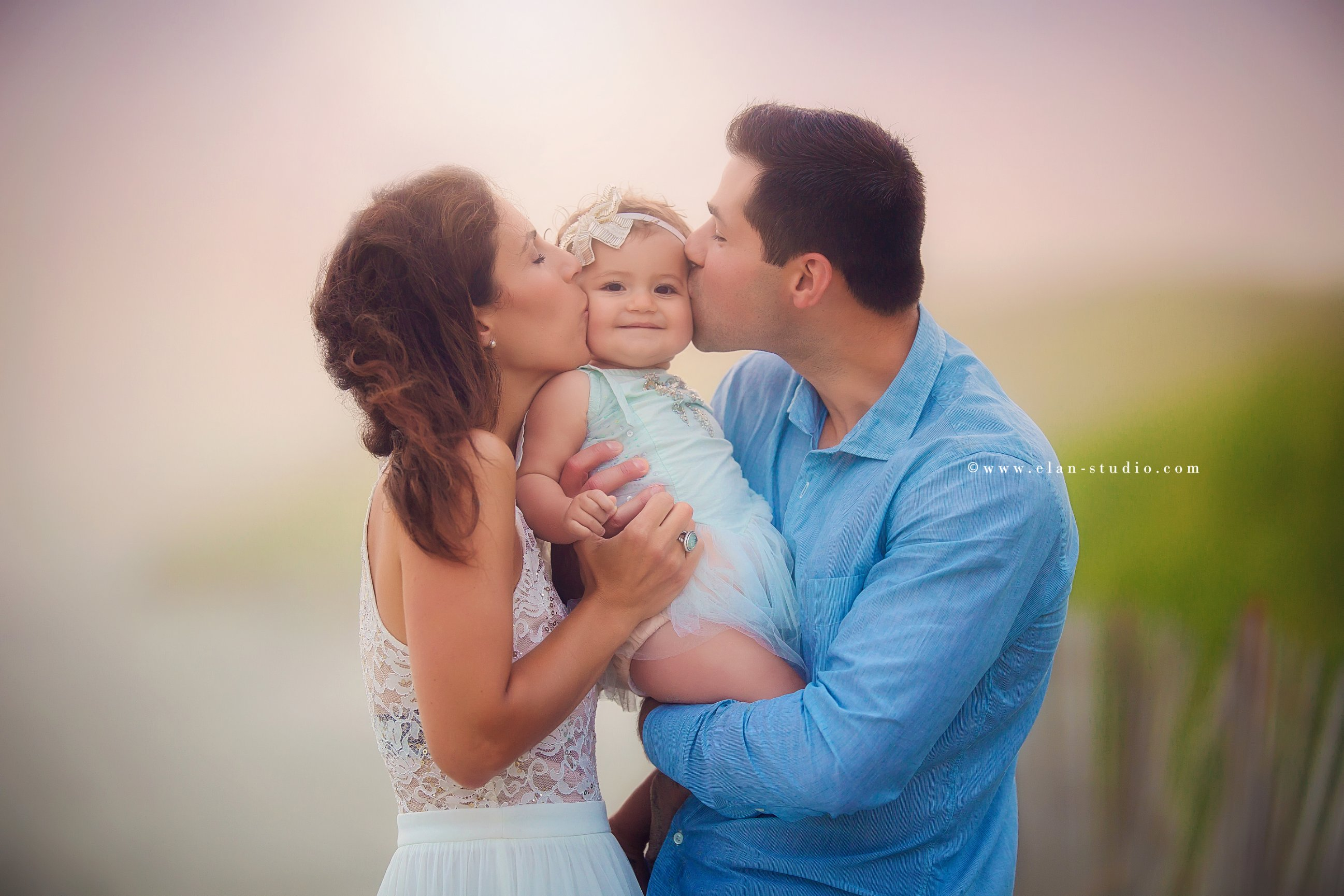 mother and father kissing baby girl at sunset