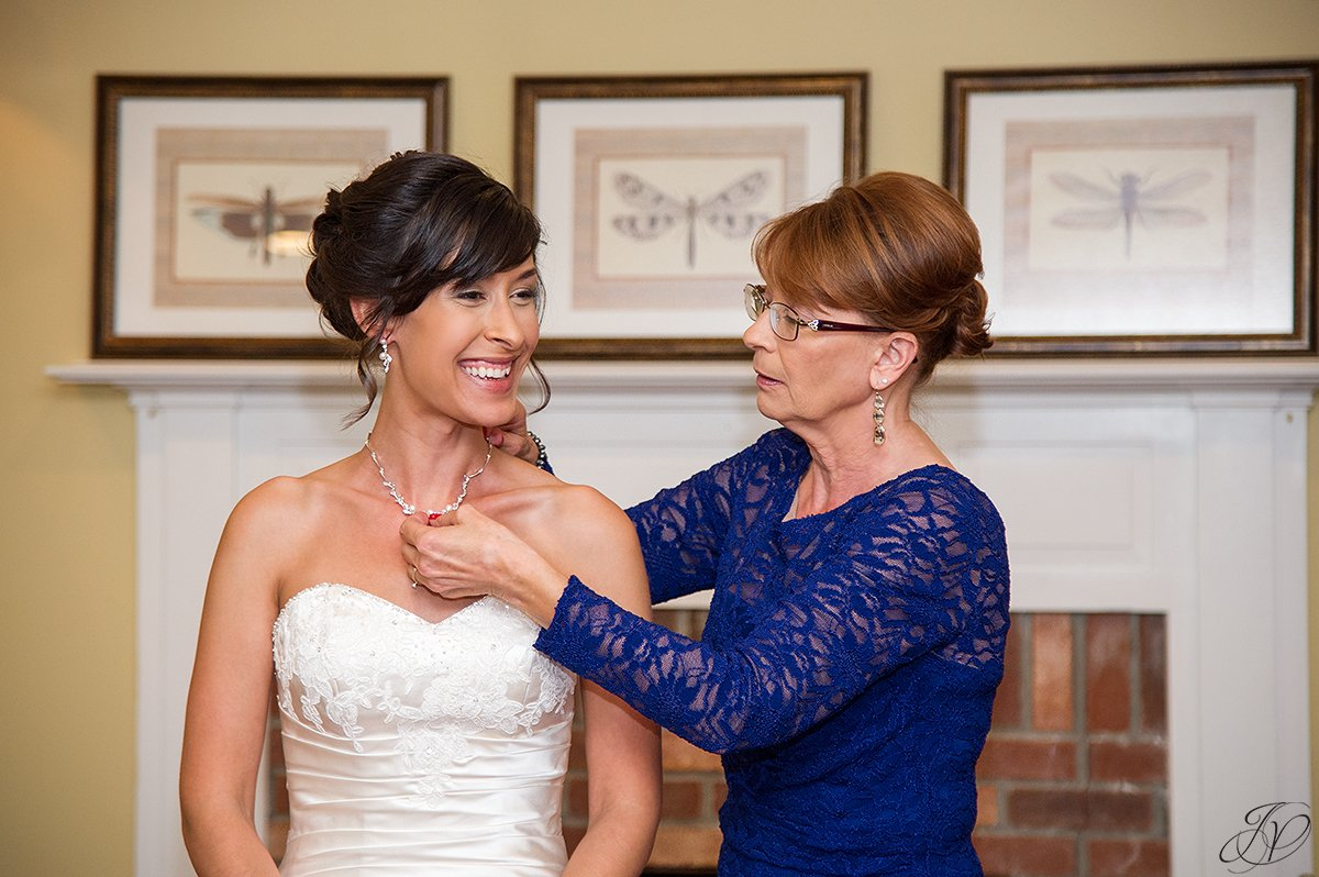 bride getting final touch help from mother