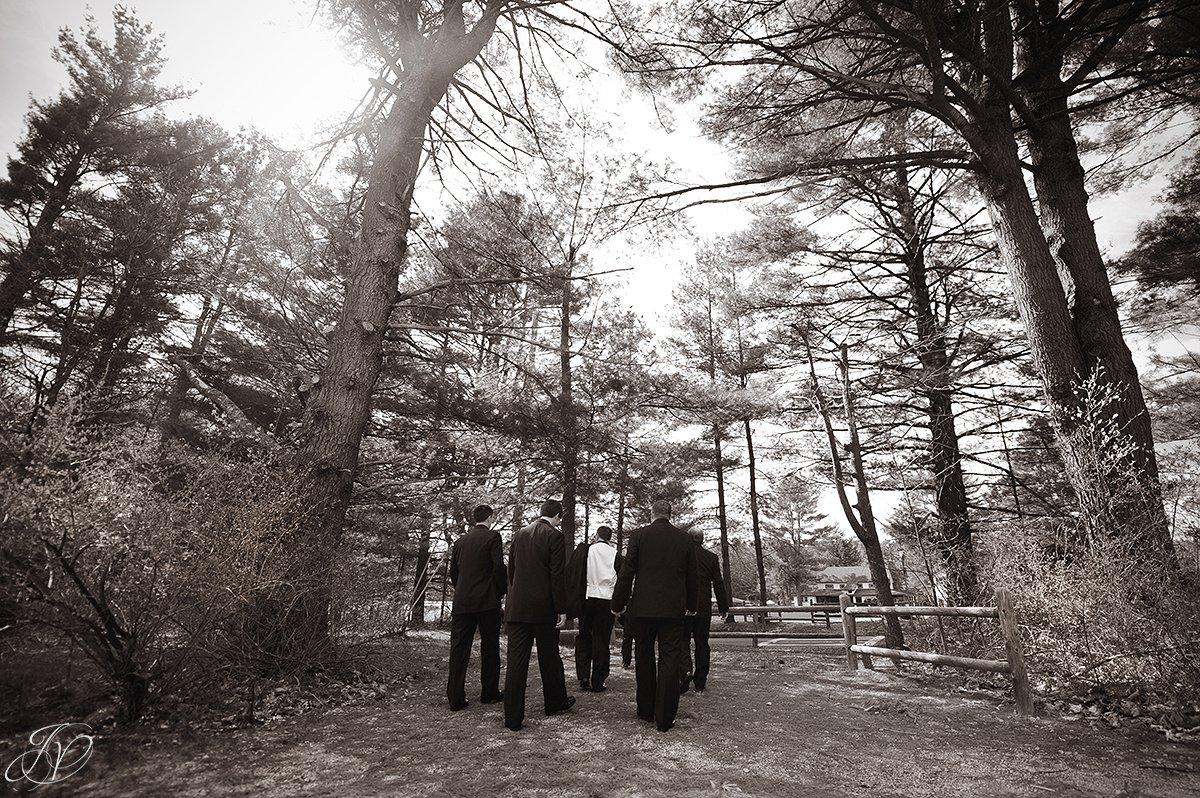 unique black and white photo of groomsmen heading to ceremony