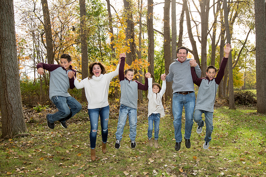 Family jumping in fall leaves