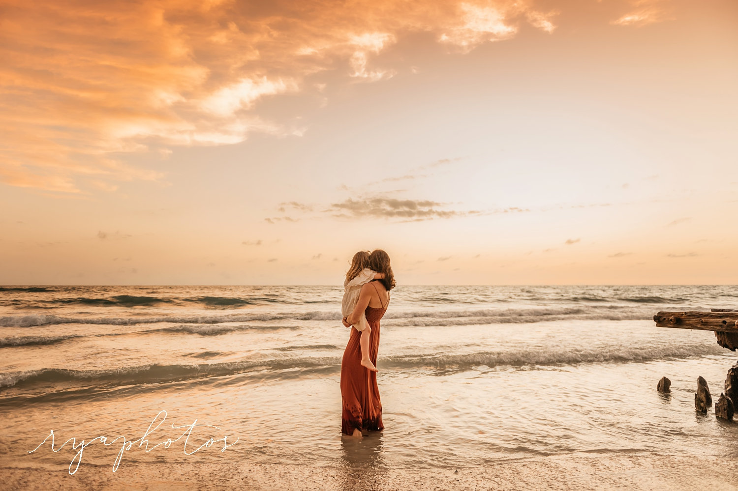 mother holding young daughter at the beach at sunset, Florida, Ryaphotos