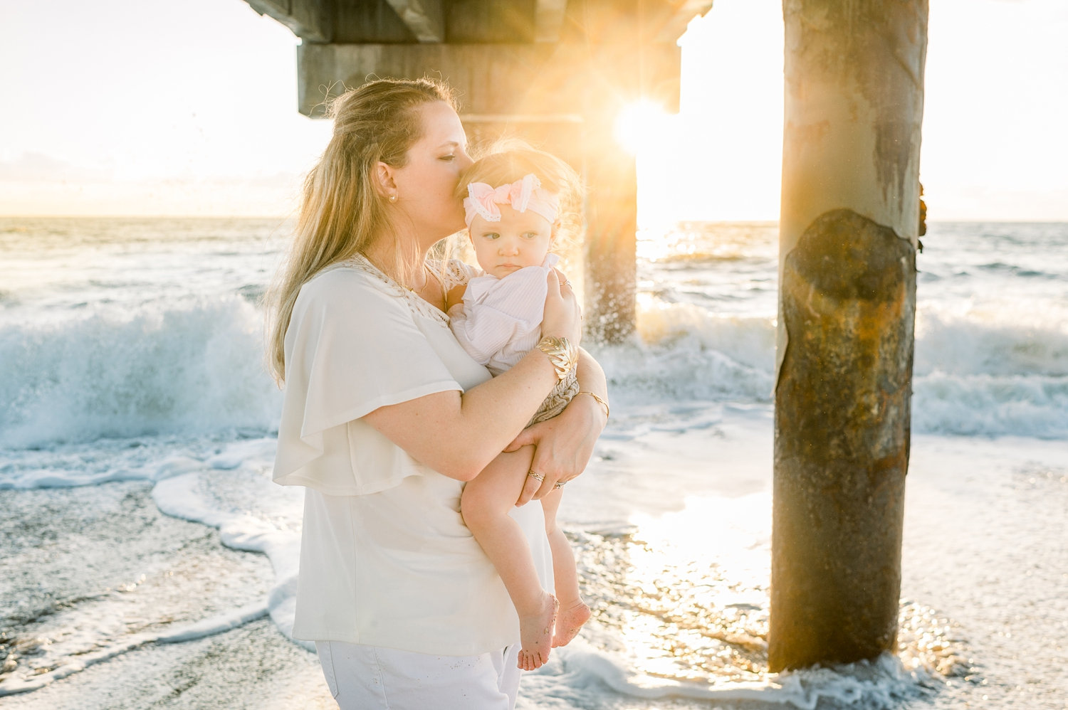 mother kissing baby girl, beach pier, sunrise beach session, Rya Duncklee