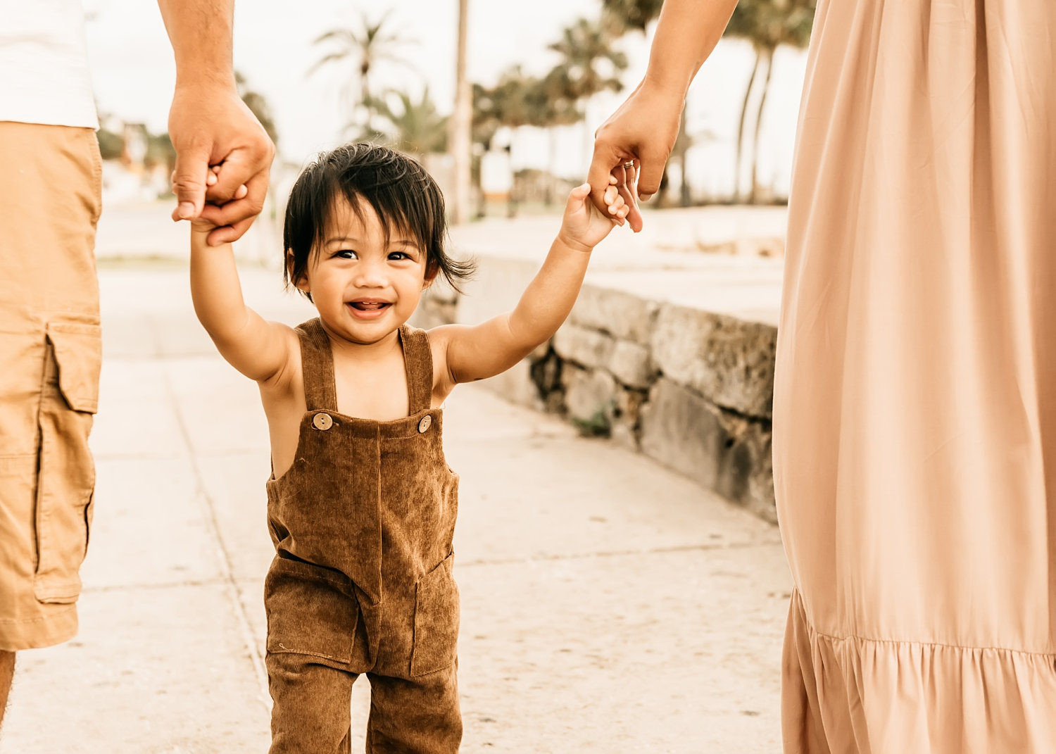 parents holding toddler boy's hands while he's walking, Saint Augustine Florida family photography